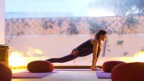 Szczęśliwej młodej kobiety ćwiczy joga na pustej klasie przy zmierzchem zbiory