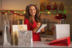 Szczęśliwej młodej kobiety sprawdza lista boże narodzenie teraźniejszość Zdjęcie Stock