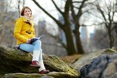 Szczęśliwej młodej kobiety turystyczny czytanie książka przy central park w Miasto Nowy Jork Żeński podróżnik cieszy się widoki w obrazy stock