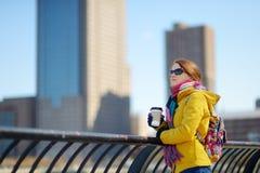 Szczęśliwej młodej kobiety turystyczny zwiedzać w Miasto Nowy Jork przy pogodnym wiosna dniem Żeński podróżnik pije kawę w w cent zdjęcie stock