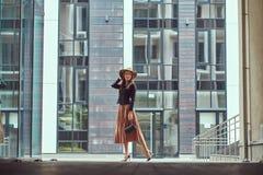 Szczęśliwej mody elegancka kobieta jest ubranym czarną kurtkę, brown kapelusz i spódnica z torebką, trzymamy mocno odprowadzenie  zdjęcia royalty free