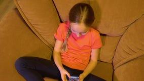 Szczęśliwej nastolatek dziewczyny przyglądająca fotografia w ogólnospołecznych środkach mądrze telefonem w wygodnym krześle zbiory