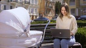 Szczęśliwej nowożytnej mamy pracujący laptop patrzeje dziecka w karecianej siedzącej parkowej ławce zbiory wideo
