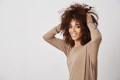 Szczęśliwej pięknej afrykańskiej dziewczyny uśmiechnięty macanie jej włosy Biały tło Obrazy Royalty Free