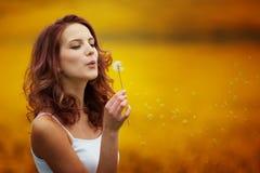 Szczęśliwej pięknej kobiety podmuchowy dandelion Zdjęcia Royalty Free