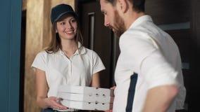 Szczęśliwej pizzy kobiety Doręczeniowe wizyty Stwarzają ognisko domowe Z pudełkami klient Dawać pieniądze pracownik i pokazywać a zbiory wideo