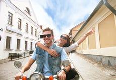 Szczęśliwej potomstwo pary jeździecka hulajnoga w miasteczku Przystojna faceta i młodej kobiety podróż Przygody i wakacji pojęcie Fotografia Stock