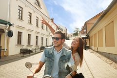 Szczęśliwej potomstwo pary jeździecka hulajnoga w miasteczku Przystojna faceta i młodej kobiety podróż Przygody i wakacji pojęcie Obraz Stock