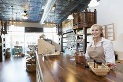 Szczęśliwej starszej żeńskiej pikantności handlowa pozycja przy kontuarem podczas gdy patrzejący daleko od w sklepie Fotografia Stock