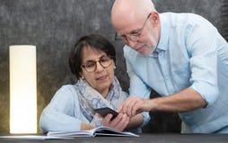 Szczęśliwej starszej pary czytelnicza wiadomość smartphone zdjęcie stock