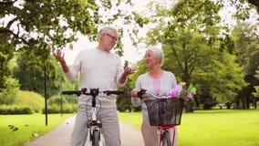 Szczęśliwej starszej pary jeździeccy bicykle przy lato parkiem zbiory wideo