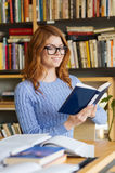 Szczęśliwej studenckiej dziewczyny czytelnicza książka w bibliotece Zdjęcie Royalty Free