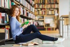 Szczęśliwej studenckiej dziewczyny czytelnicza książka w bibliotece Fotografia Stock