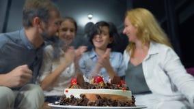 Szczęśliwej uśmiechniętej chłopiec podmuchowe świeczki na jej urodzinowym torcie dzieci otaczający ich rodziną urodzinowego torta zbiory