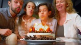 Szczęśliwej uśmiechniętej chłopiec podmuchowe świeczki na jej urodzinowym torcie dzieci otaczający ich rodziną urodzinowego torta obrazy royalty free