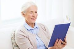 Szczęśliwej uśmiechniętej starszej kobiety czytelnicza książka w domu Fotografia Royalty Free