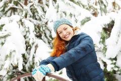Szczęśliwi ładni rudzielec młodej kobiety stojaki obok ławki w zima parku zdjęcia stock