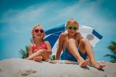 Szczęśliwi śliczni dzieciaki chłopiec i dziewczyna bawić się na plaży fotografia royalty free