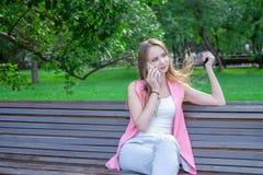 Szczęśliwi śliczni młoda kobieta uśmiechy i opowiadać na telefonie w parku obraz stock