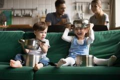 Szczęśliwi śmieszni dzieciaki bawić się z kitchenware kucharstwem puszkują w domu zdjęcia stock