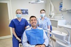 Szczęśliwi żeńscy dentyści z mężczyzna pacjentem przy kliniką Zdjęcie Stock