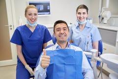 Szczęśliwi żeńscy dentyści z mężczyzna pacjentem przy kliniką Fotografia Stock