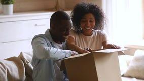 Szczęśliwi afrykańscy para klienci otwierają karton satysfakcjonującego z zakupem zdjęcie wideo