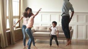 Szczęśliwi amerykanin afrykańskiego pochodzenia rodzice i śliczni dzieciaki tanczy w domu zbiory