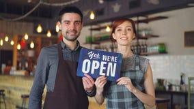 Szczęśliwi atrakcyjni ludzie cukiernianych pracowników w fartuchach trzymają ` tak stojący inside jesteśmy otwartym ` znakiem i o zbiory