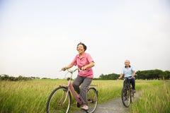 Szczęśliwi Azjatyccy starsi seniory dobierają się jechać na rowerze w parku z błękitem