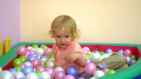 Szczęśliwi berbecie śmia się i bawić się w wielo- coloured balowym basenie preschool zbiory wideo