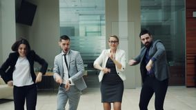 Szczęśliwi biznes drużyny mężczyźni i kobiety tanczą przy pracy przyjęciem wpólnie rusza się ciała, śmia się relaksować wewnątrz  zbiory