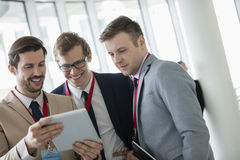 Szczęśliwi biznesmeni używa cyfrową pastylkę przy convention center obraz royalty free