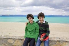 Szczęśliwi bliźniacy są przy plażą Fotografia Stock
