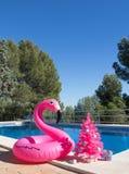 szczęśliwi Boże Narodzenie wakacje Flaminga boja jest ubranym Santa kapelusz z różową choinką basenem zdjęcie royalty free