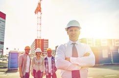 Szczęśliwi budowniczowie i architekt przy budową Zdjęcie Royalty Free