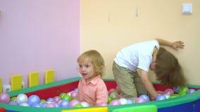 Szczęśliwi caucasian berbecie śmia się i bawić się w wielo- coloured balowym basenie preschool zdjęcie wideo