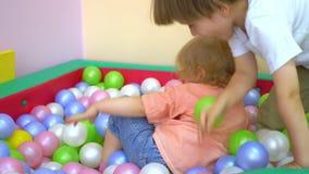 Szczęśliwi caucasian berbecie ma zabawę i bawić się w wielo- coloured balowym basenie preschool zdjęcie wideo