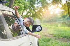 Szczęśliwi chłopiec spojrzenia od za auto okno i witają somebody, Szczęśliwi dzieciaki podróżują samochodem zdjęcie royalty free