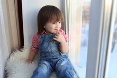 Szczęśliwi chłopiec spojrzenia z okno w wintertime Obrazy Royalty Free