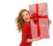 Szczęśliwi czerwoni boże narodzenia zawijający młoda kobieta chwyta prezent przedstawia smilin Zdjęcie Stock