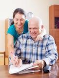 Szczęśliwi dojrzali pary czytania dokumenty w domu Zdjęcia Royalty Free