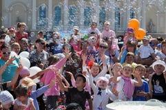 Szczęśliwi dzieci łapią mydlanych bąble na ulicie w mieście T Obrazy Royalty Free
