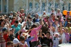 Szczęśliwi dzieci łapią mydlanych bąble na ulicie w mieście T Zdjęcie Royalty Free