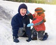 Szczęśliwi dzieci bawić się na śnieżnym wzgórzu troszkę Obrazy Royalty Free