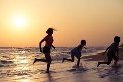 Szczęśliwi dzieci bawić się na plaży przy zmierzchu czasem Fotografia Stock