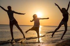Szczęśliwi dzieci bawić się na plaży przy zmierzchu czasem obrazy stock