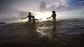 Szczęśliwi dzieci bawić się na plaży przy zmierzchu czasem zbiory wideo