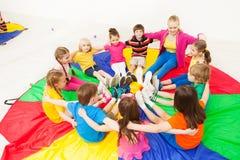 Szczęśliwi dzieci bawić się okrąg gry z nauczycielem fotografia stock