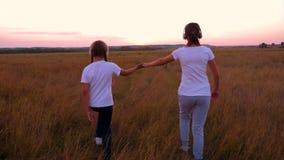 Szczęśliwi dzieci chodzą przez śródpolne mienie ręki Dzieci sen i podróż dzieci w hełmofonach słuchają muzyka zdjęcie wideo